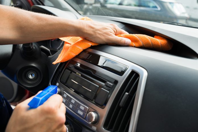 Worker Cleaning Car Dashboard