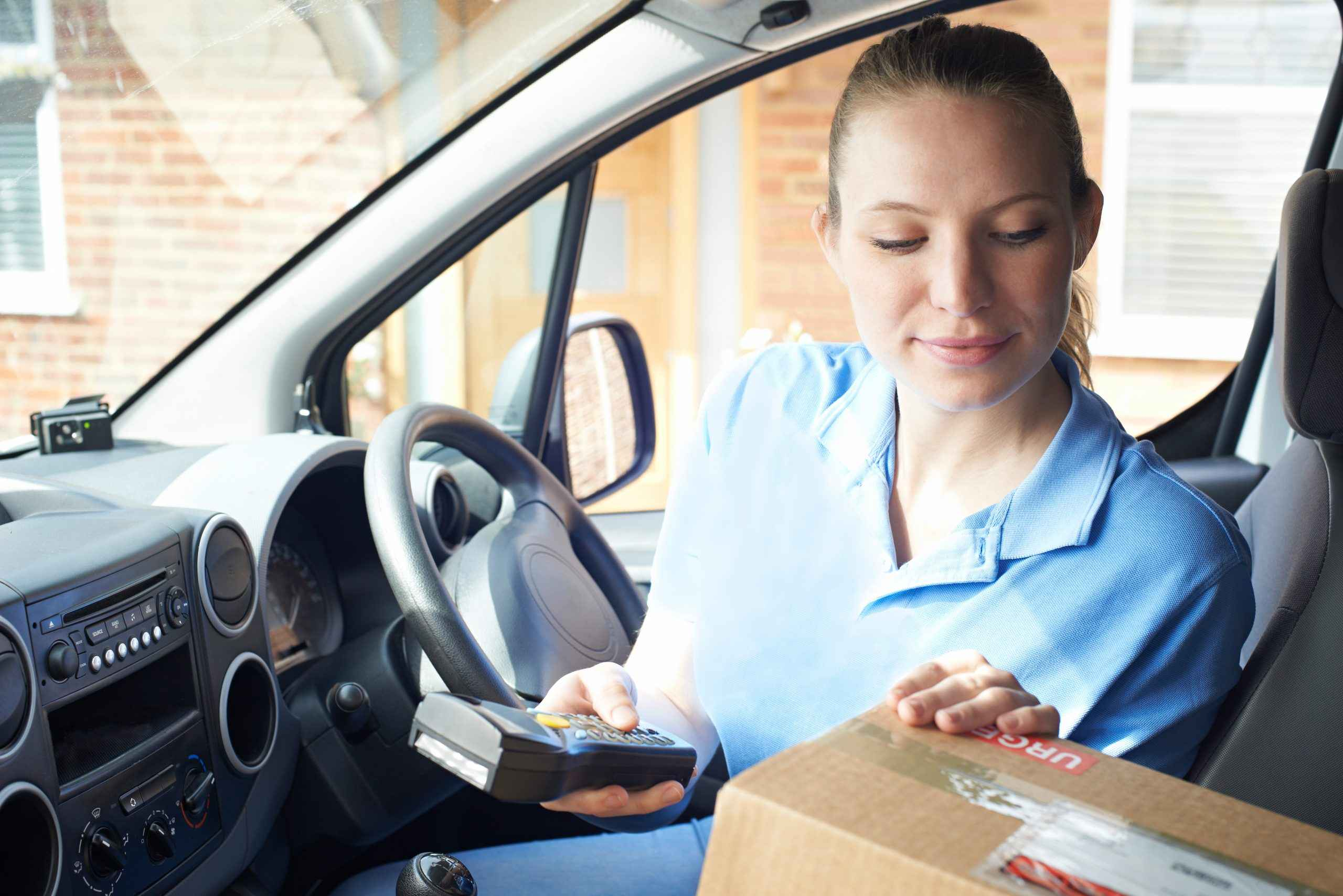 Female courier checking a parcel inside a van