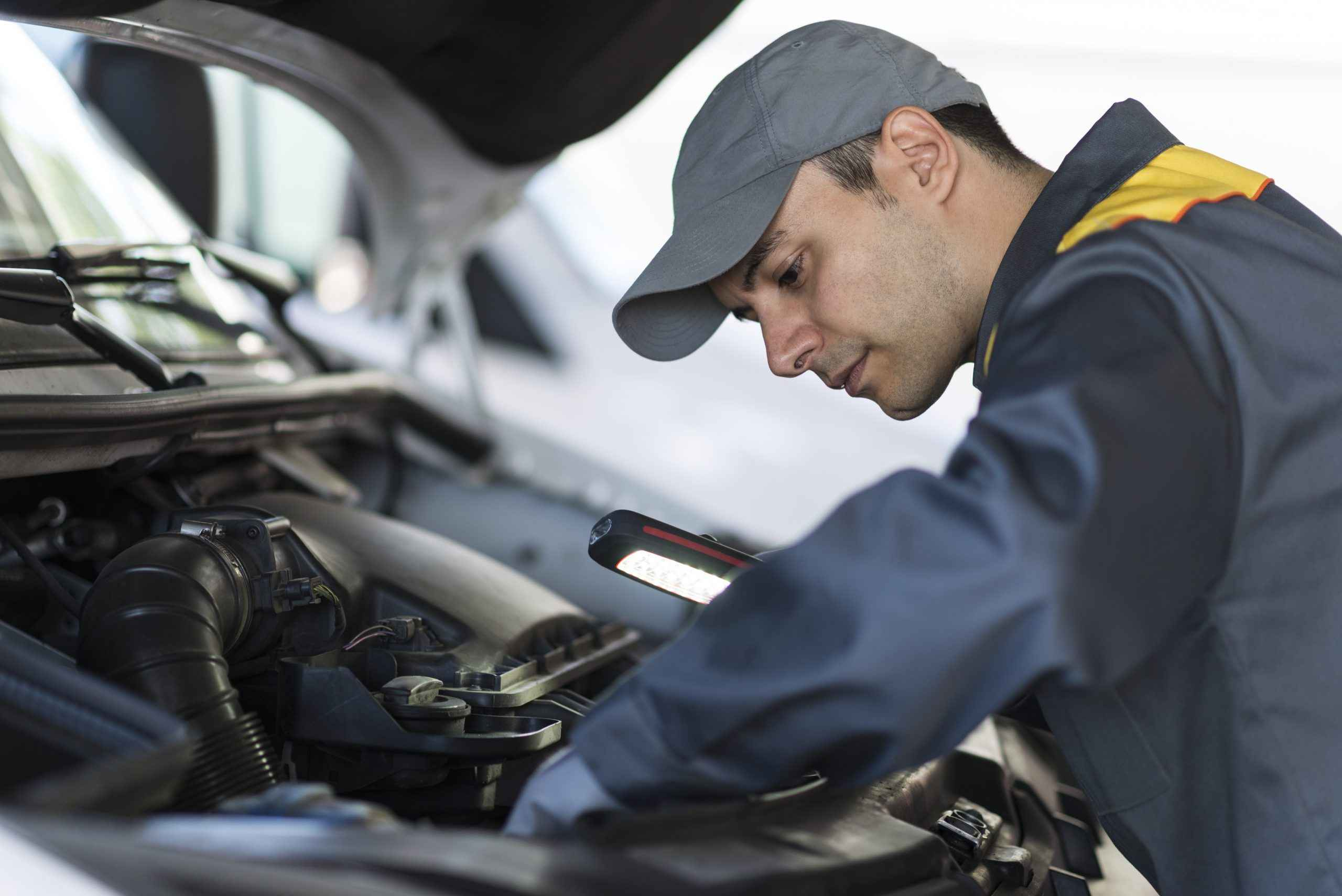 Mechanic inspecting a vehicle under the bonnet