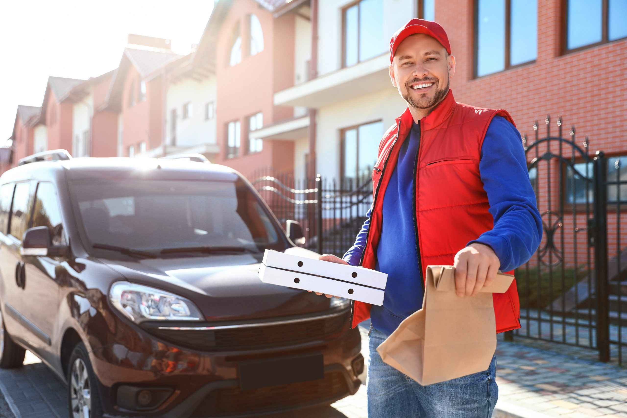 Fast food delivery driver with pizza boxes in hand
